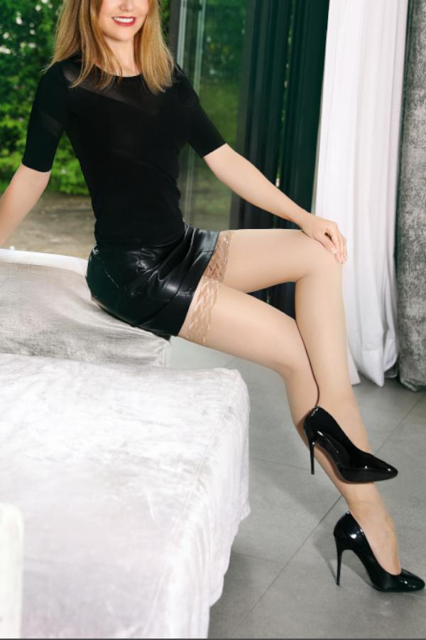 Nicole - Escort Model München im schwarzen Kleid auf einem Sofa sitzend.