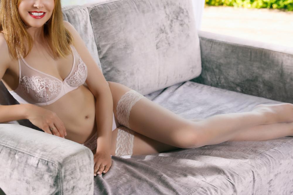 Nicole - Escort Model München in weissen Dessous auf einem grauen Sofa liegend mit einem breiten Lächeln im Gesicht.